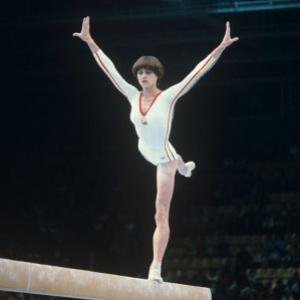 Rumunská gymnastka. Do histórie sa zapísala tým, že na bradlách dostala ako jediná 100% hodnotenie (10.0), čo sa odvtedy nikdy nikomu nepodarilo: